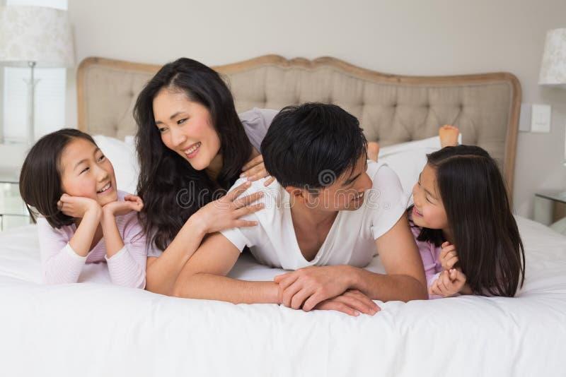 Famille de quatre gaie se situant dans le lit image stock