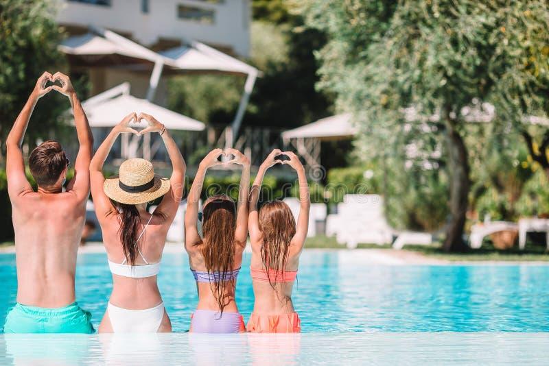 Famille de quatre heureuse dans la piscine d'extérieur photo stock