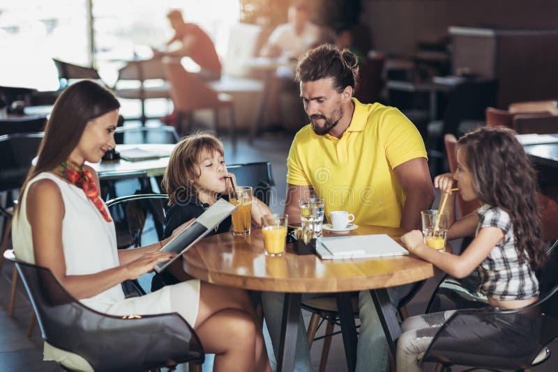 Famille de quatre membres ayant le grand temps dans un restaurant images stock