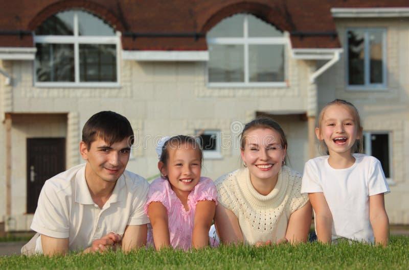Famille de quatre mensonges sur l'herbe contre la maison photo libre de droits