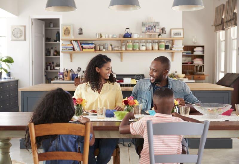 Famille de quatre noire prenant le déjeuner dans leur cuisine à la maison image stock