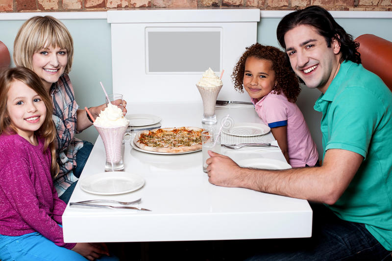 Famille de quatre posant à l'appareil-photo photo stock