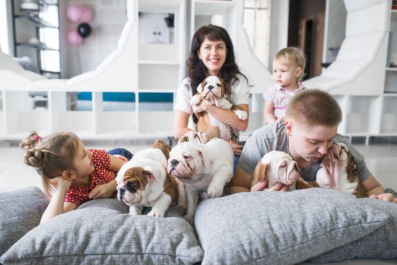 Famille de quatre se trouvant sur le tapis avec des chiots photos stock