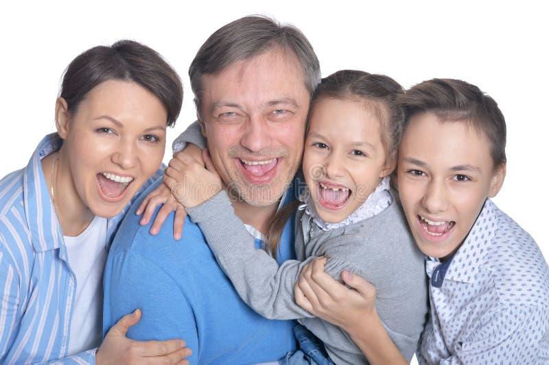 Famille de quatre de sourire heureuse posant sur le fond blanc photographie stock libre de droits