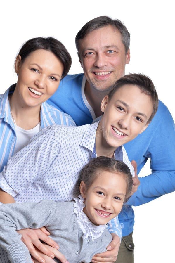 Famille de quatre de sourire heureuse posant sur le fond blanc photo libre de droits