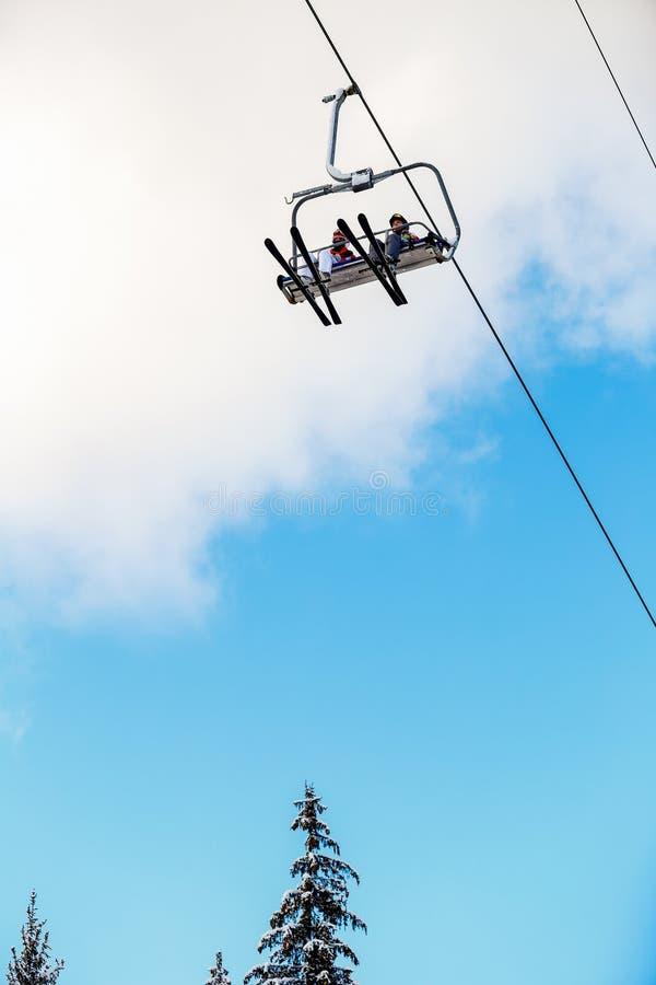 Famille de ski de vue inférieure sur l'ascenseur de chaise photo stock