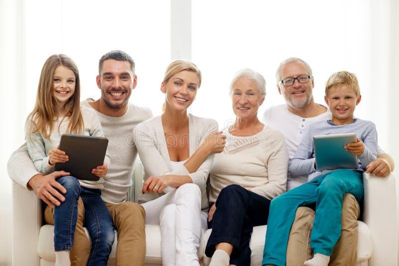 Famille de sourire avec le PC de comprimé à la maison photos stock
