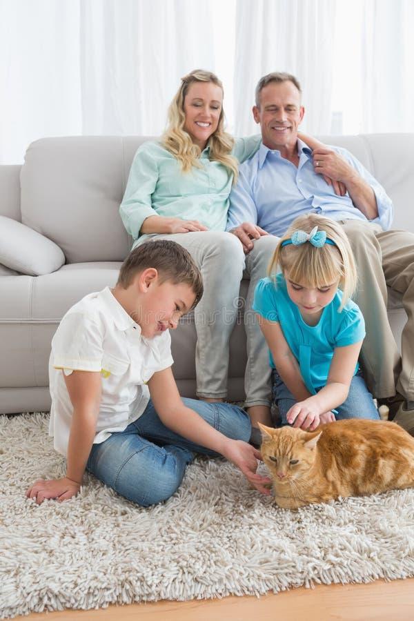 Famille de sourire avec leur chat de gingembre sur la couverture images libres de droits