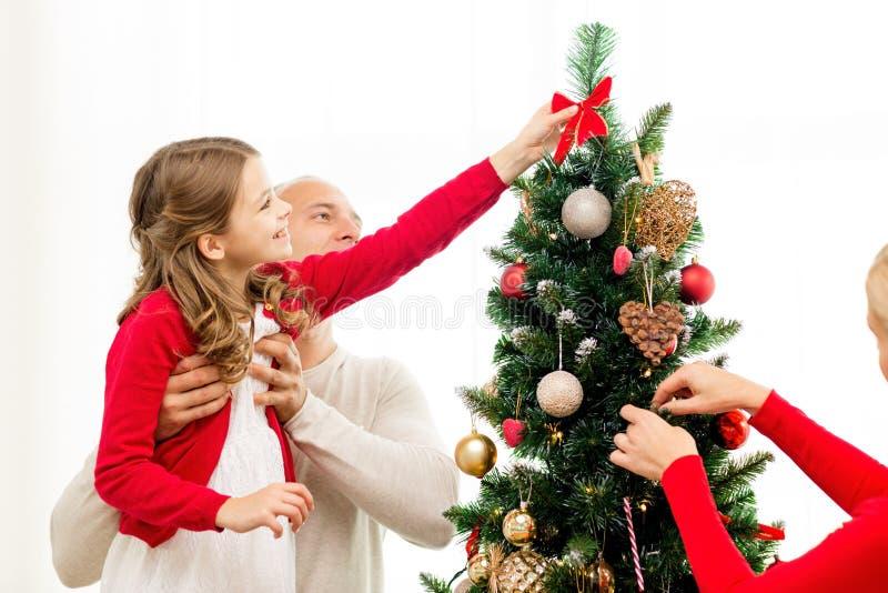 Famille de sourire décorant l'arbre de Noël à la maison photos libres de droits