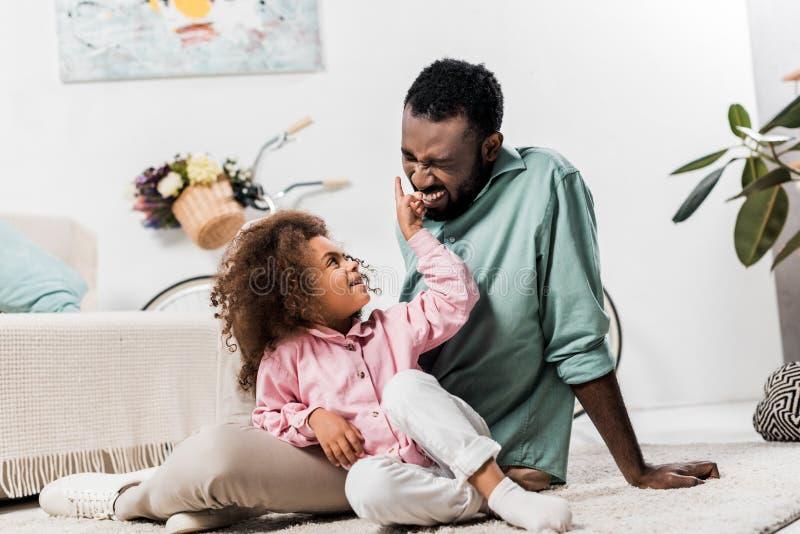 famille de sourire d'afro-américain s'asseyant sur la couverture et le jeu photos stock