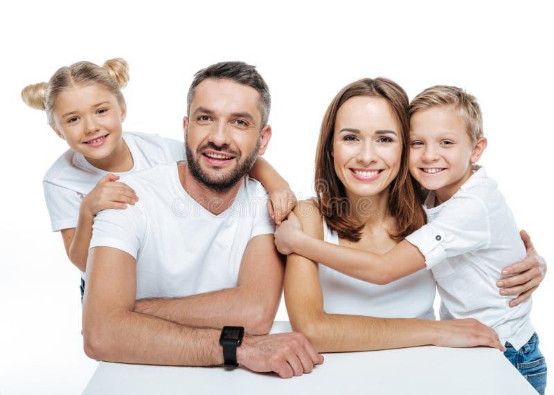 Famille de sourire dans étreindre blanc de T-shirts photos libres de droits