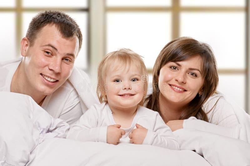 Famille de sourire dans le lit images stock