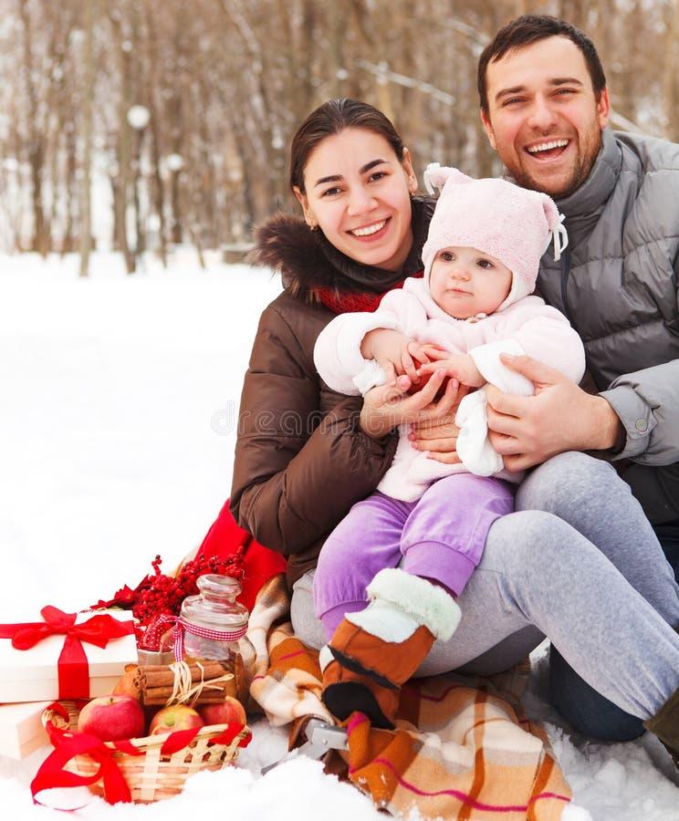 Famille de sourire heureuse avec au pique-nique d'hiver photographie stock