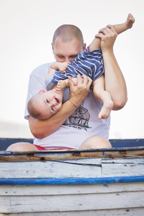 Famille de sourire heureuse de gros père audacieux et de petit nourrisson mignon photos stock
