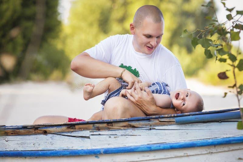 Famille de sourire heureuse de gros père audacieux et de petit nourrisson mignon images stock