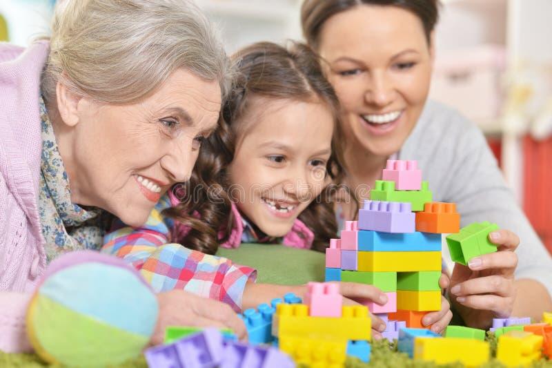 Famille de sourire heureuse jouant avec les blocs en plastique color?s photo libre de droits