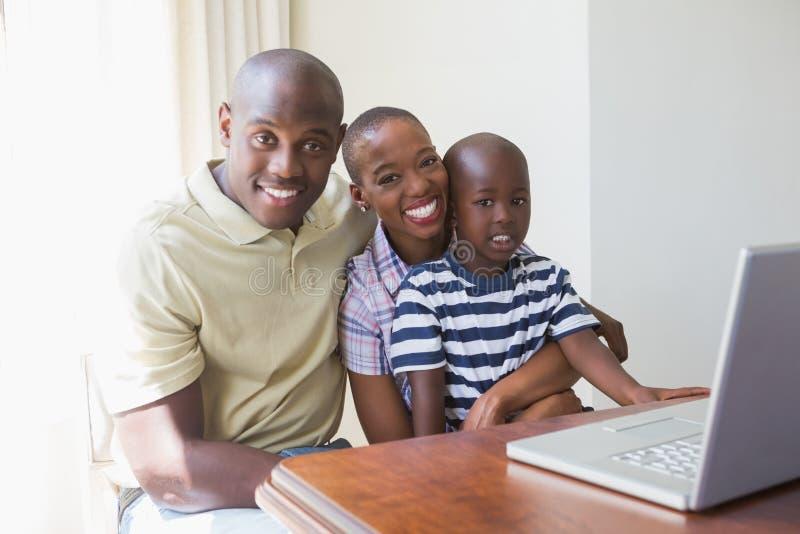 Download Famille De Sourire Heureuse Utilisant L'ordinateur Portable Photo stock - Image du enfant, père: 56484532
