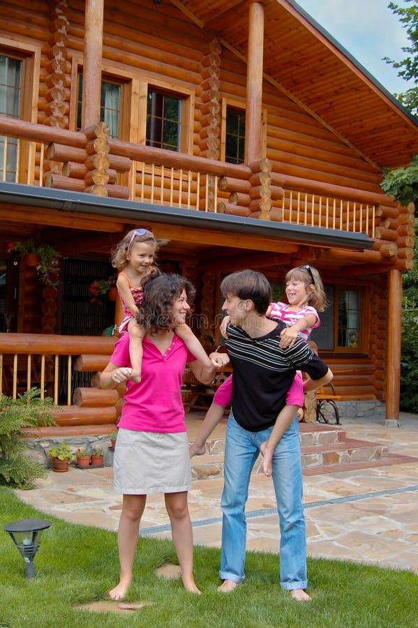 Famille de sourire heureux près de maison en bois photos stock
