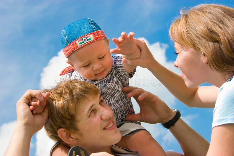 Famille de sourire heureux sur le fond de ciel bleu photos libres de droits