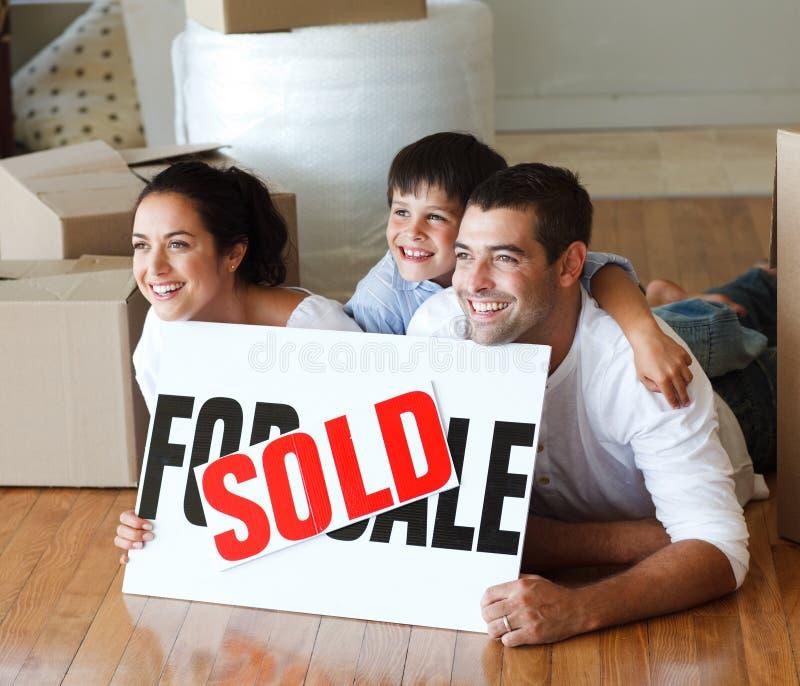 Famille de sourire sur l'étage après l'achat de la maison images stock