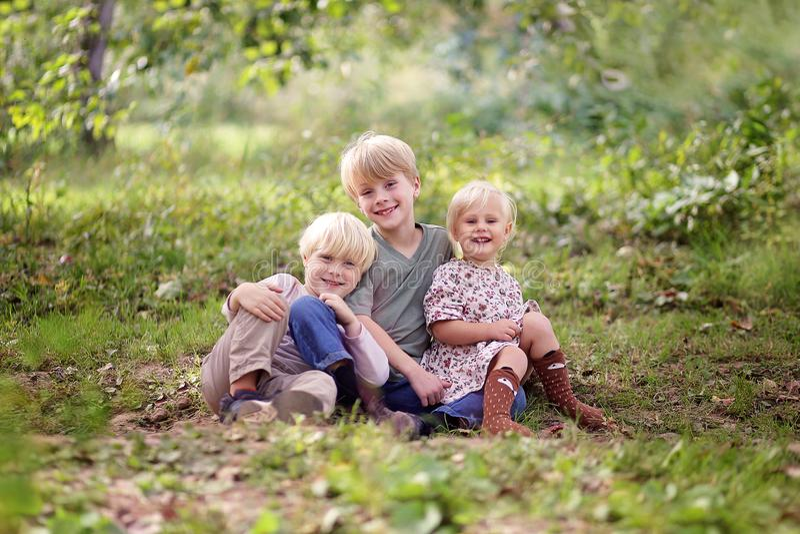 Famille de trois enfants en bas âge heureux posant dehors dans la forêt images libres de droits