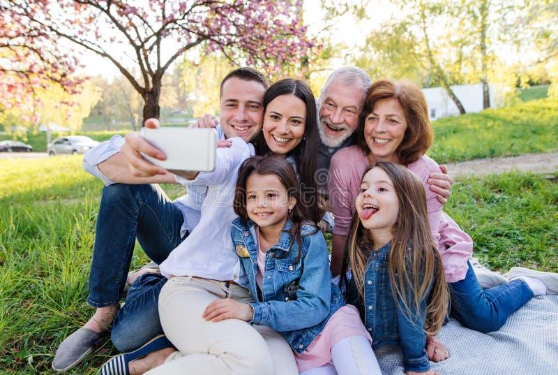 Famille de trois générations assise à l'extérieur de la nature printanière, prenant le selfie images stock