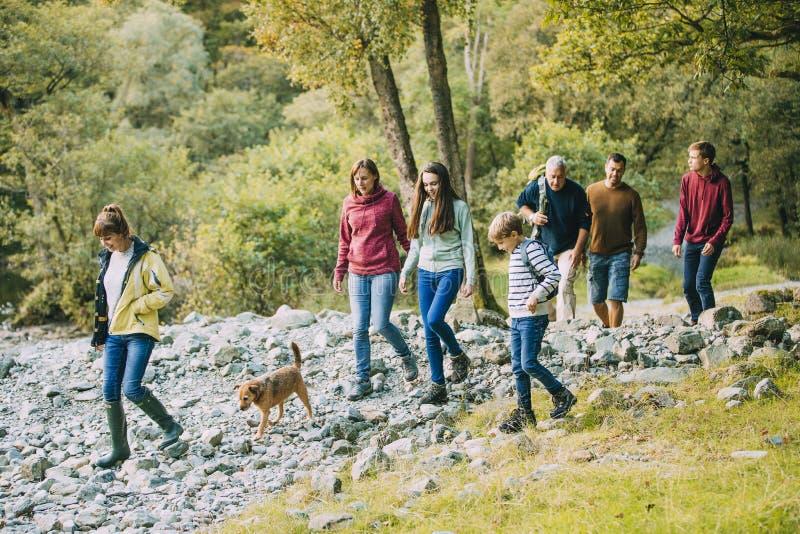 Famille de trois générations augmentant par le secteur de lac photographie stock libre de droits