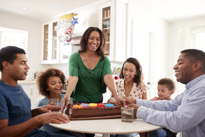 Famille de famille de trois générations se reposant ensemble dans la cuisine célébrant un anniversaire, grand-mère apportant le g images libres de droits