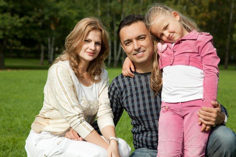Famille de trois heureuse à l'extérieur photographie stock libre de droits