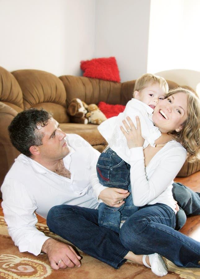 Famille de trois heureuse à la maison photographie stock