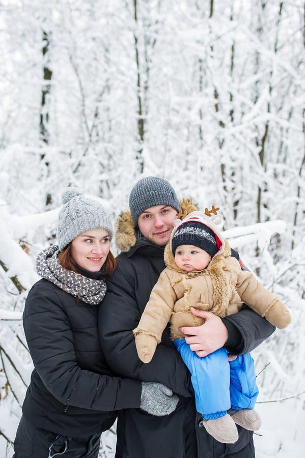 Famille de trois heureuse dans la perspective des arbres couverts de neige image libre de droits