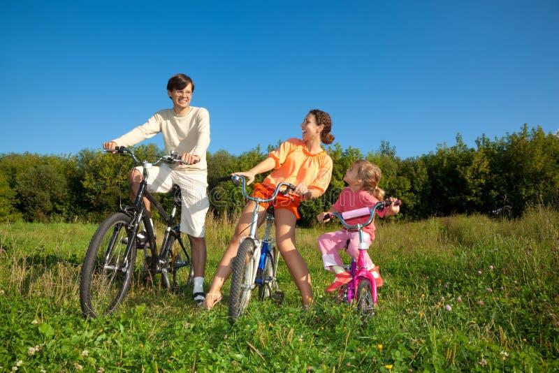 Famille de trois personnes sur des bicyclettes dans le pays. photos libres de droits