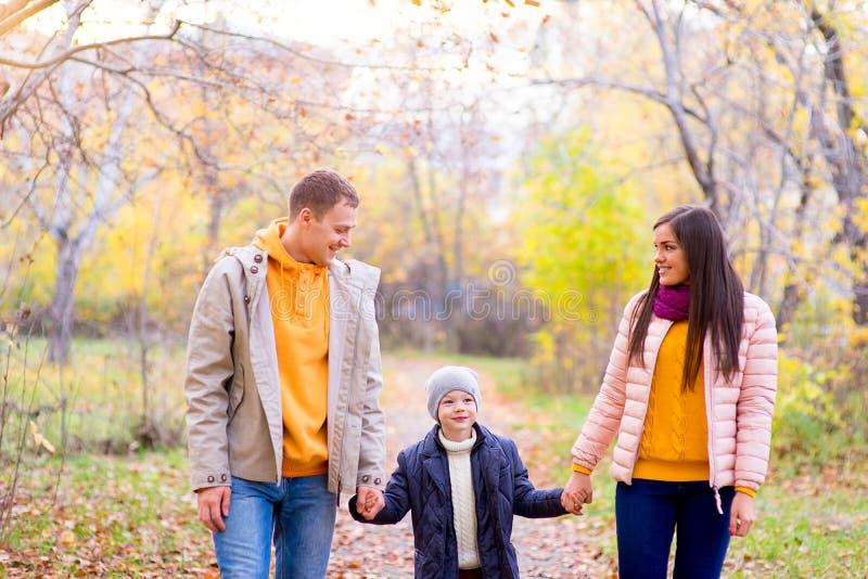 Famille de trois promenades en parc d'automne image libre de droits