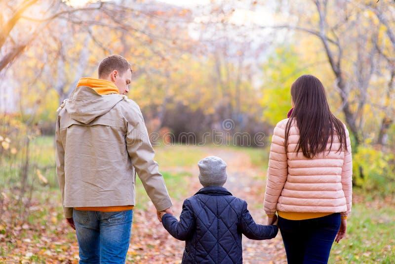 Famille de trois promenades en parc d'automne photo libre de droits