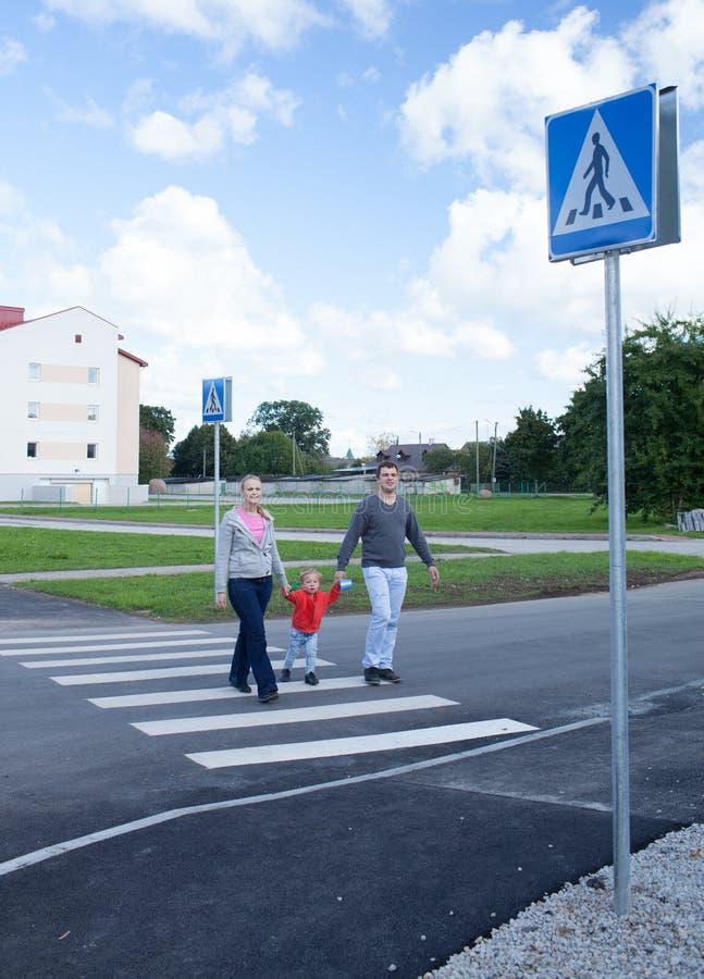 Famille de trois traversant la route. photos libres de droits