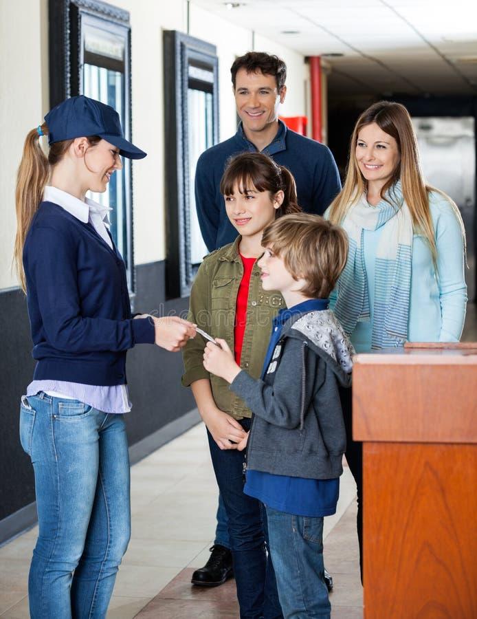 Famille donnant le billet au travailleur pour l'examen à photographie stock