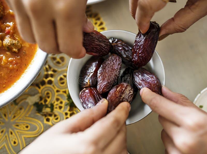 Famille du Moyen-Orient partageant et mangeant des dates ensemble photos stock