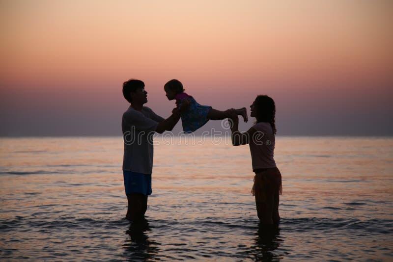 Famille en mer sur le coucher du soleil photographie stock