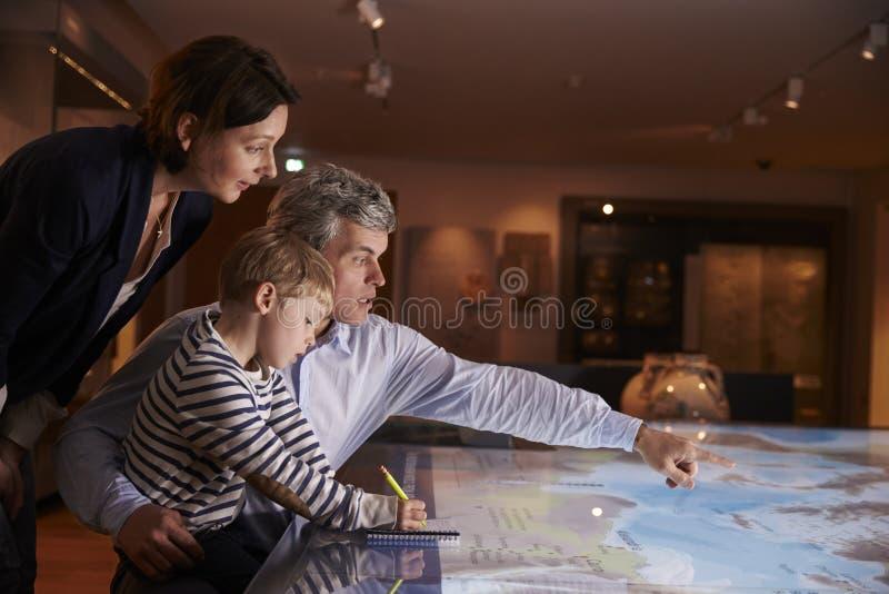 Famille en voyage au musée regardant la carte ensemble image libre de droits
