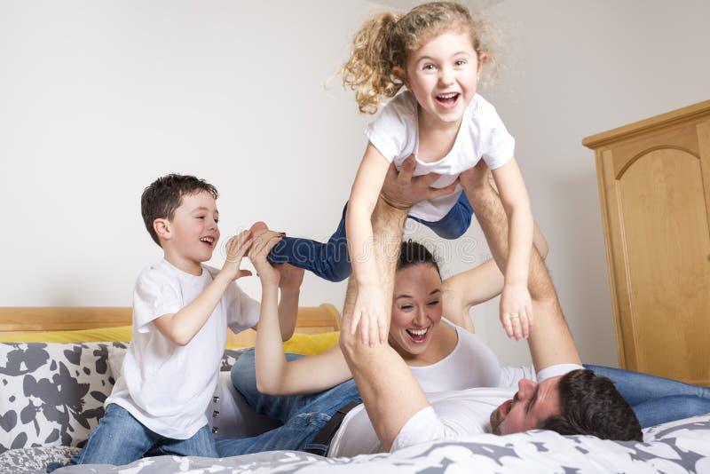 Famille, enfants et concept à la maison - famille heureuse avec deux enfants sous la couverture à la maison photo libre de droits