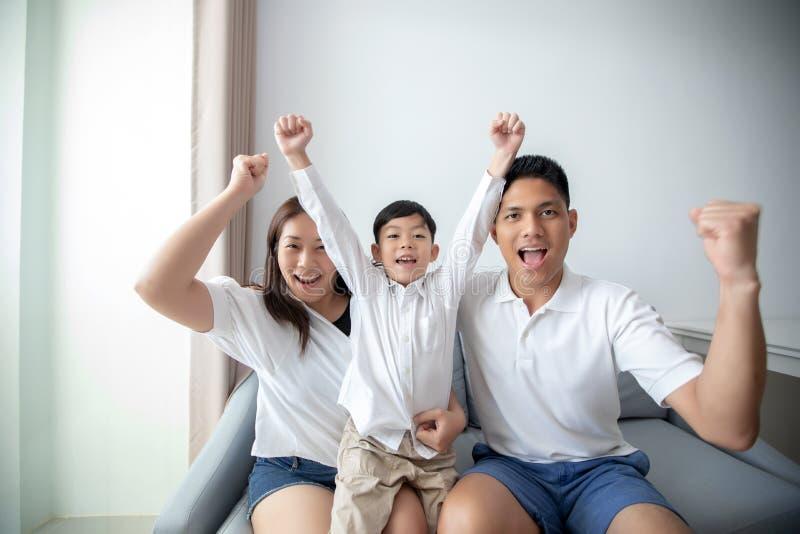 Famille enthousiaste et heureuse avec des bras augmentés tout en observant des televis image stock