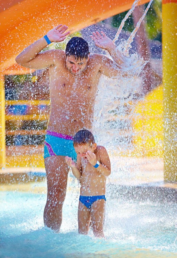Famille enthousiaste heureuse sous le courant de l'eau dans le parc aquatique photographie stock