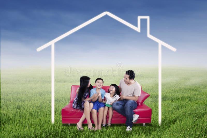 Famille enthousiaste s'asseyant sous la maison rêveuse photographie stock