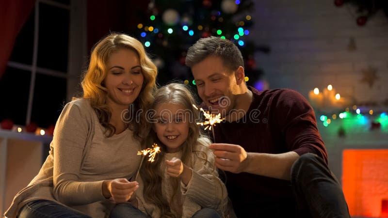Famille enthousiaste tenant la lumière de Bengale se reposant sous l'arbre de Noël, soirée du Nouveau an image stock