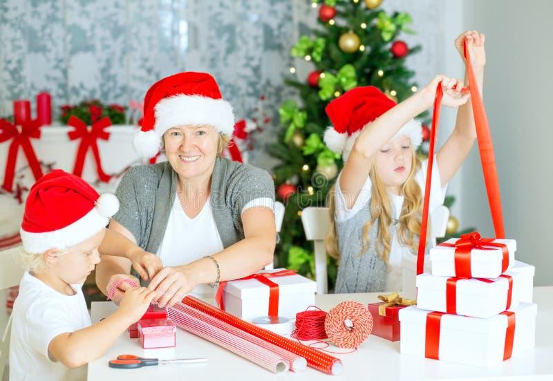 Famille enveloppant des cadeaux de Noël photo libre de droits