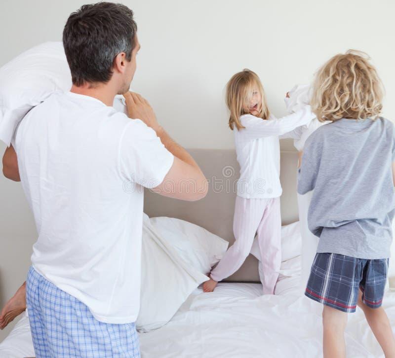 Famille espiègle ayant un combat d'oreiller photos libres de droits