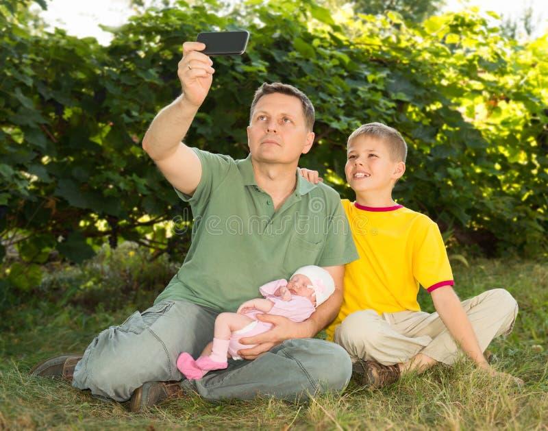 Famille et concept de parenting Famille heureuse prenant le selfie avec le SM images libres de droits