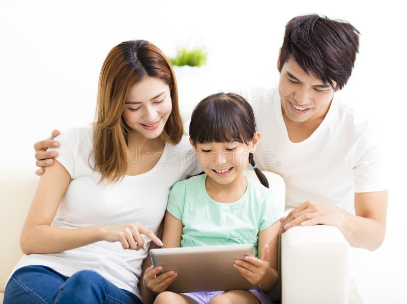 Famille et fille heureuses à l'aide du comprimé sur le sofa photo stock