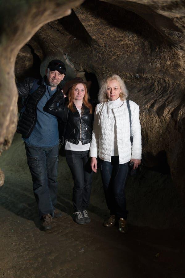 Famille explorant la caverne énorme Les voyageurs d'aventure ont habillé le chapeau de cowboy et le sac à dos, un groupe de perso image stock