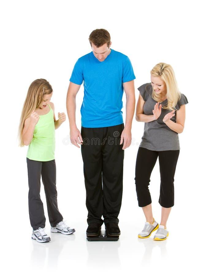 Famille : Famille excitée que l'homme perd le poids photographie stock